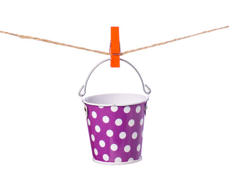 A bucket of clothespins rope on a white background isolation