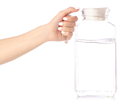 A decanter jug with water in hand on a white background isolation Stock Photo