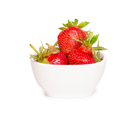 Strawberries in white bowl on a white background isolation 写真素材