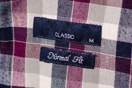 Size M textile clothes label tag normal fit on cage red gray black white cotton background Banco de Imagens