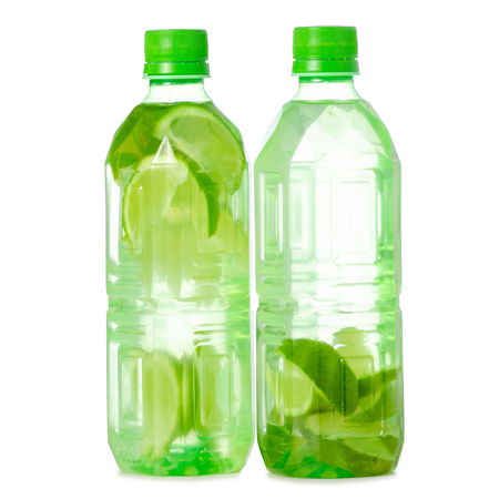 Two bottles of water with lime on white background isolation Stock Photo