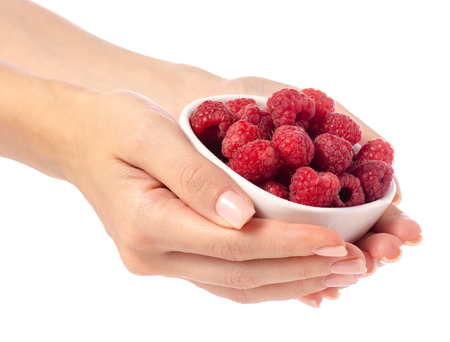 Raspberries in a bowl in hand on a white background isolation