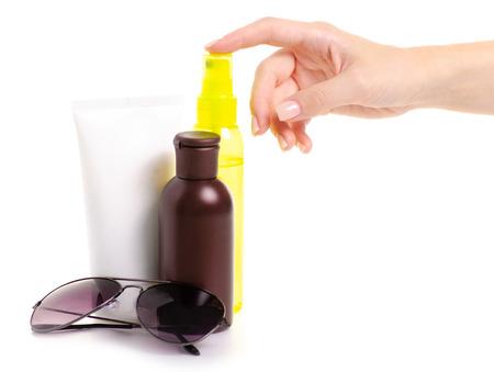 Cream oil spray for suntan sun glasses female hand on white background isolation