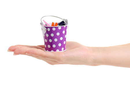 A small bucket with clothespins in hand on a white background isolation Stock Photo