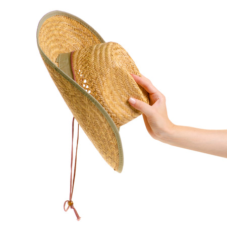 Straw hat in hand on white background isolation
