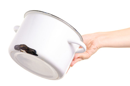 Old enamel saucepan battered in hand on white background isolation