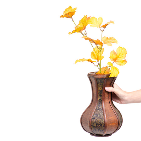 Wooden vase autumn leaves in hand on white background isolation