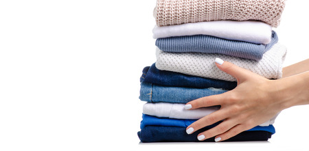 Stack of clothing jeans sweaters in hand on a white background isolation