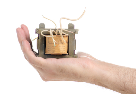 Electrical transformer power in hand isolated on a white background.