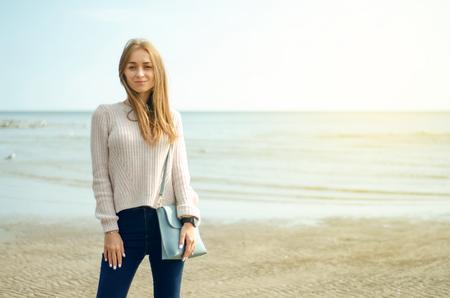 Belle femme dans un pull jeans chaussures femme sac montre sur un fond de nature soleil