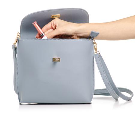 Una mano ha messo un lucidalabbra cosmetico nella borsa di pelle grigio blu femminile su un isolamento di sfondo bianco Archivio Fotografico