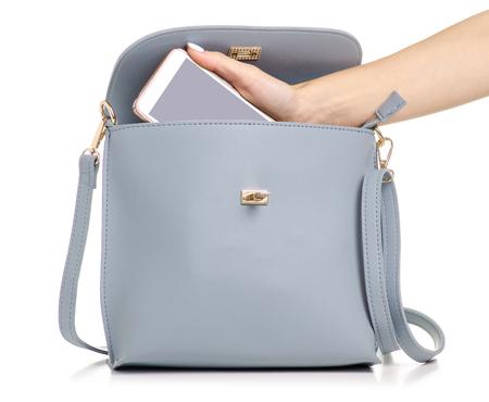 Una mano puso el teléfono en el bolso de cuero gris azul femenino sobre un fondo blanco aislamiento Foto de archivo