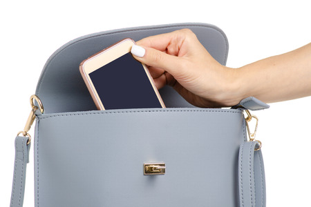 A hand put the phone in the female blue gray leather handbag on a white background isolation Reklamní fotografie
