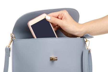 Une main a mis le téléphone dans le sac à main en cuir gris bleu femelle sur un isolement de fond blanc Banque d'images