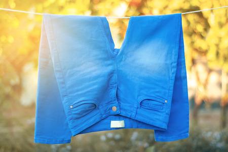 Jean bleu accroché à une pince à linge nature sur fond flou