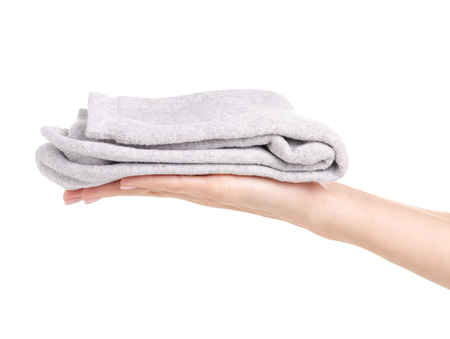 Gray socks in hand on a white background isolation