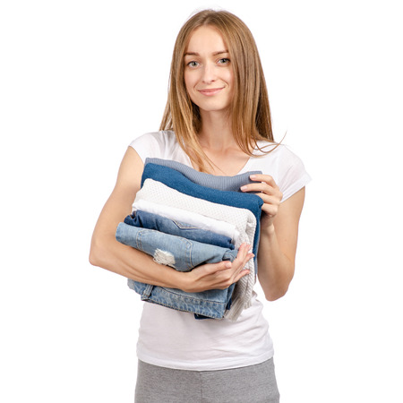 A stack of sweaters jeans in the hands of a woman on a white background. Isolation 스톡 콘텐츠