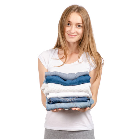 A stack of sweaters jeans in the hands of a woman isolated on a white background.