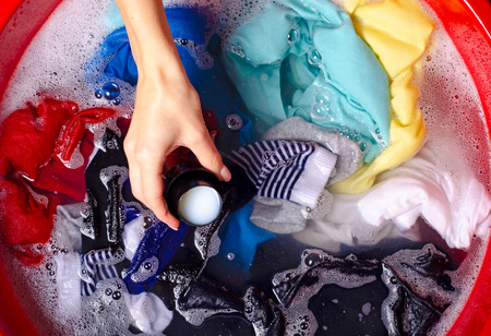 Women washing color clothes in basin enemale powdered detergent liquid laundry gel, top view