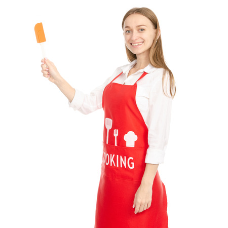 A woman in a red apron in the hands of a kitchen spatula isolated on a white background. Фото со стока - 112665129