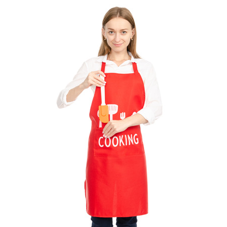 A woman in a red apron in the hands of a kitchen spatula isolated on white background. Фото со стока - 112583357