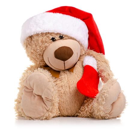 Oso de juguete de Navidad con gorro de Papá Noel aislado en un fondo blanco.