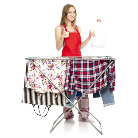 Woman in apron clothes drying rack with clean clothes plastic bottle for liquid laundry detergent isolated on a white background.