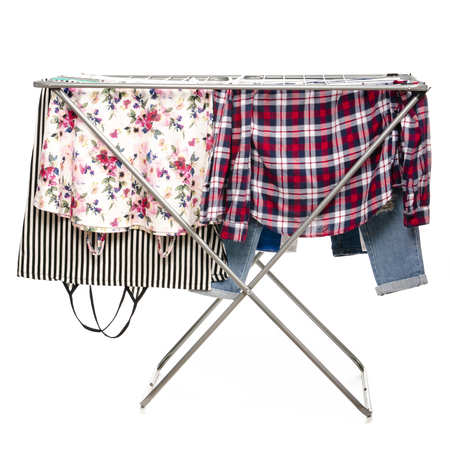 The clothes drying rack with clean clothes isolated on white background.