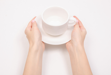 White saucer cup in hand isolated on a white background.