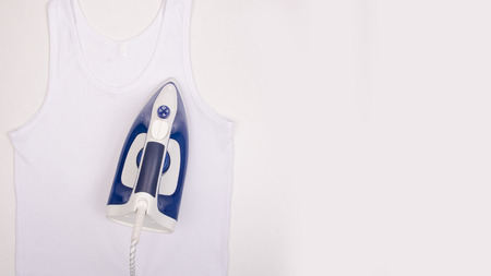 Blue iron and white shirt on ironing board top view, household. Isolated on a white background. Stock Photo