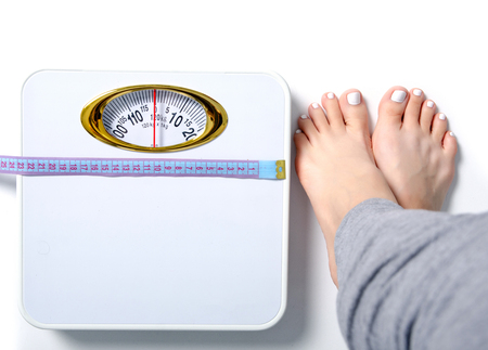 Females feet weighing scale centimeter isolated on white background.