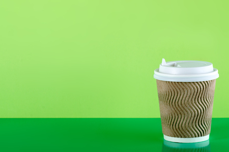 Cardboard cup of coffee on green background Stock Photo