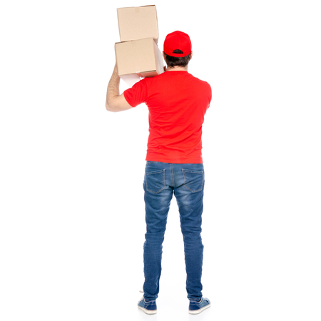 Delivery man in red uniform holding box package back view isolated on white background