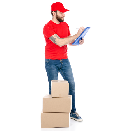 Delivery man in red uniform holding box package isolated on white background Imagens - 114765884