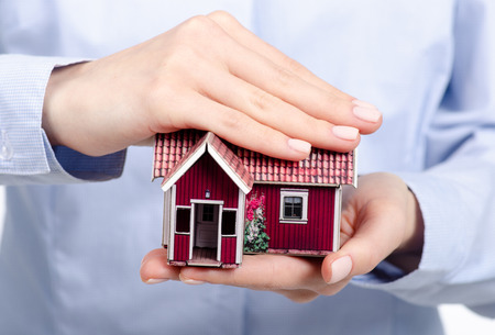 Hands holding Family small house model isolated on white background, protect house