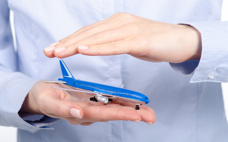 Small airplane in woman's hands isolated on white background. Travel safety concept, insurance concept