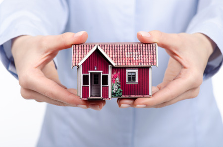 Hands holding Family small house model on white background, protect house