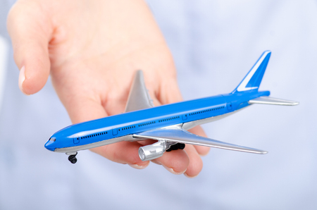 Small airplane in woman's hand isolated on white background. Travel safety concept, insurance concept