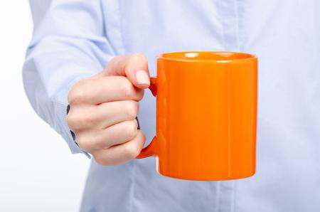 Woman's hand holding an orange mug isolated on white background
