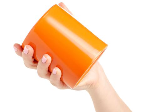Orange cup mug in female hand on white background isolation