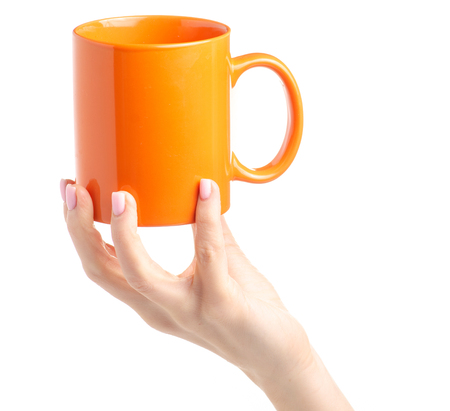 Orange cup mug in female hand on white background isolation