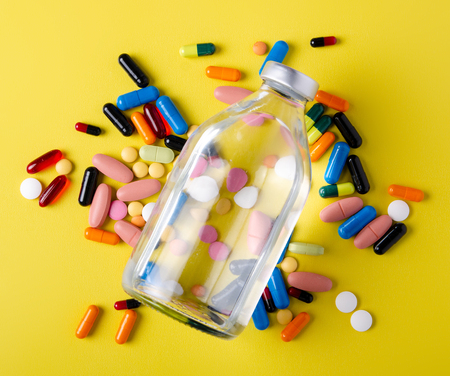 Pills capsules medicine bottle health on yellow background top view, medical pharmacy concept