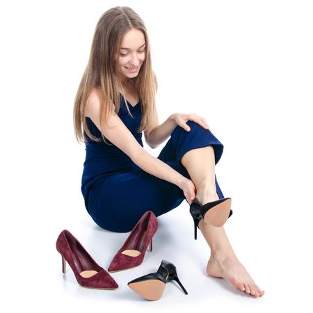 Mujer sentada elige zapatos de tacón sobre fondo blanco. Aislamiento