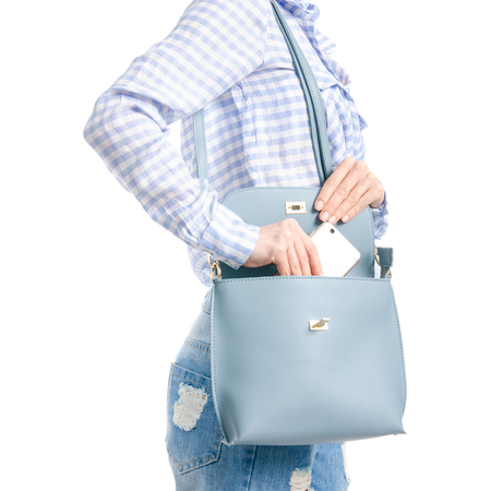 Woman in jeans and blue shirt put smartphone in blue bag macro isolated on white background.