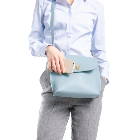 Woman in gray pants and blue shirt blue bag smartphone in hand macro isolated on white background.