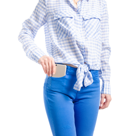 Woman in jeans and blue shirt put smartphone in pocket macro isolated on white background.