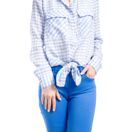 Woman in blue jeans and blue shirt hand in pocket macro isolated on white background.
