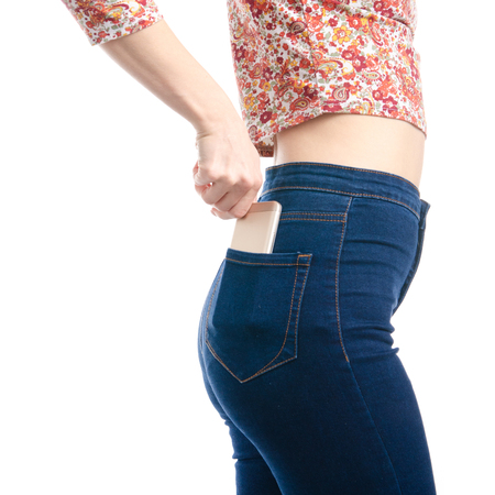 Woman in blue jeans and shirt put smartphone in pocket macro isolated on white background.