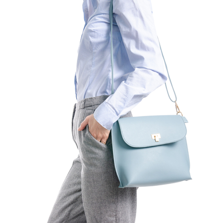 Woman in gray pants and blue shirt blue bag in hand macro isolated on white background.