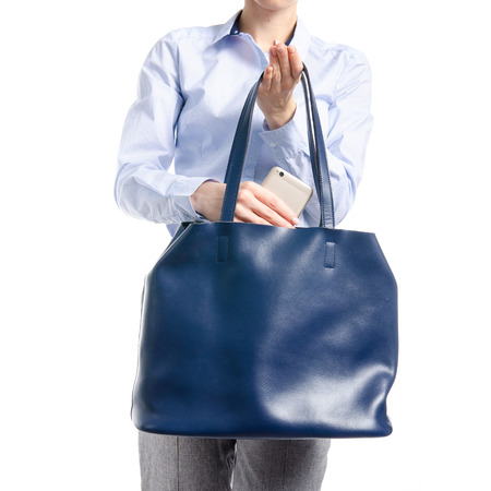 Woman in gray pants and blue shirt put smartphone in blue bag macro isolated on white background.
